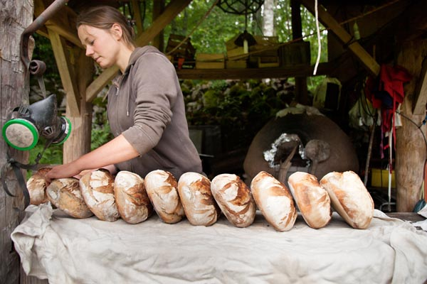 Julie bakes bread for the Ardheia community in the clay oven by Ashley Fischer